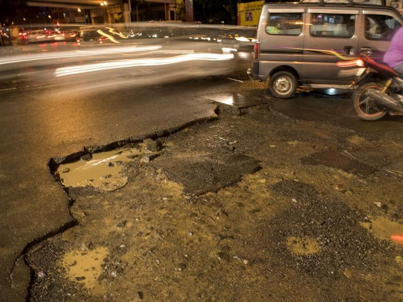 Sahar Road, Andheri: This road near Bahar Cinema is taken by commuters heading towards Vile Parle. A few showers have created craters, making the stretch prone to accidents.  (Satish Bate/ Hindustan Times)