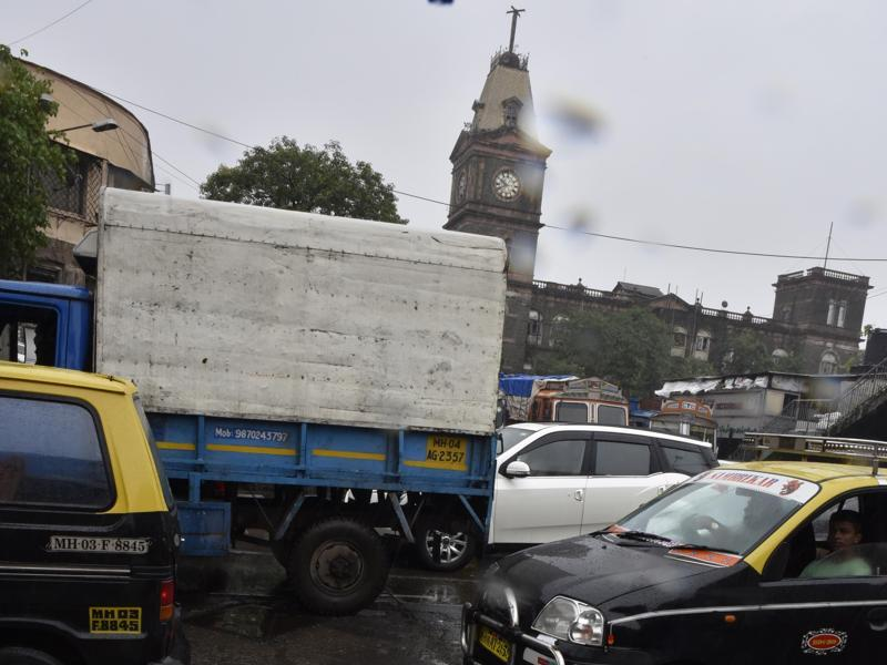 P' Dmello Road, Ghadiyal Godi: It is an arterial road in south Mumbai. Travel is a daily hassle for officegoers as they have to find a way through the potholes.  (Anshuman Poyrekar/ Hindustan Times)