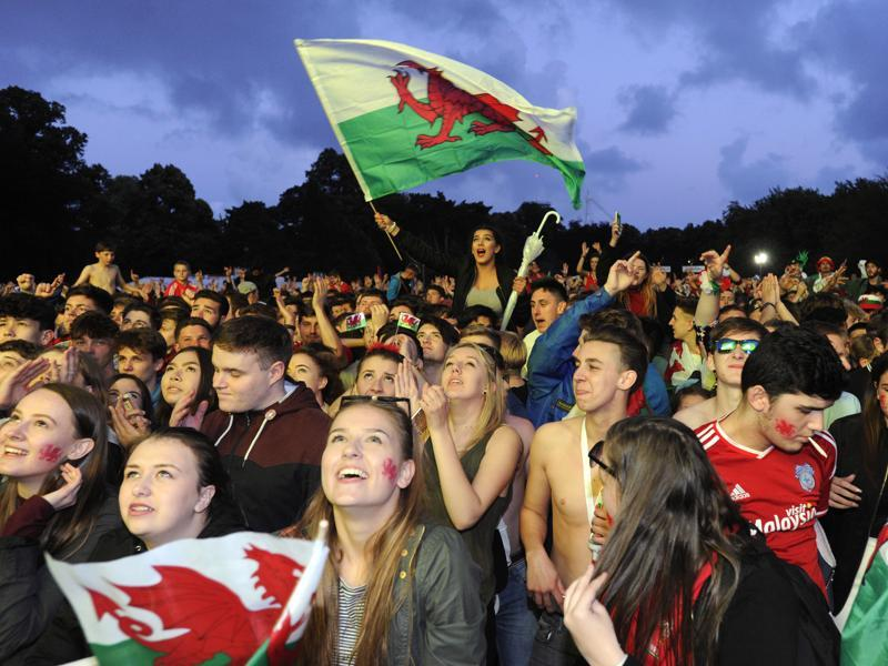 Welsh fans cheer the third goal scored by Wales during the team's match against Belgium, being shown on a big screen in the Fanzone, Coopers Field, Cardiff, Wales. (Reuters Photo)