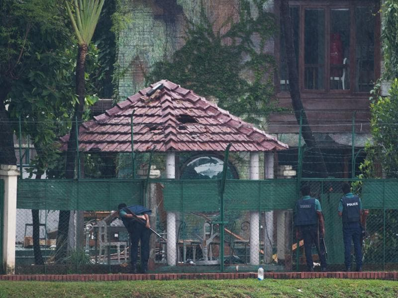 Three Bangladeshi policemen look into the back garden of the scene of the attack on Sunday, a day after a bloody siege ended with the death of 20 foreign hostages. Bangladesh began observing two days of national mourning on Sunday. (AFP)