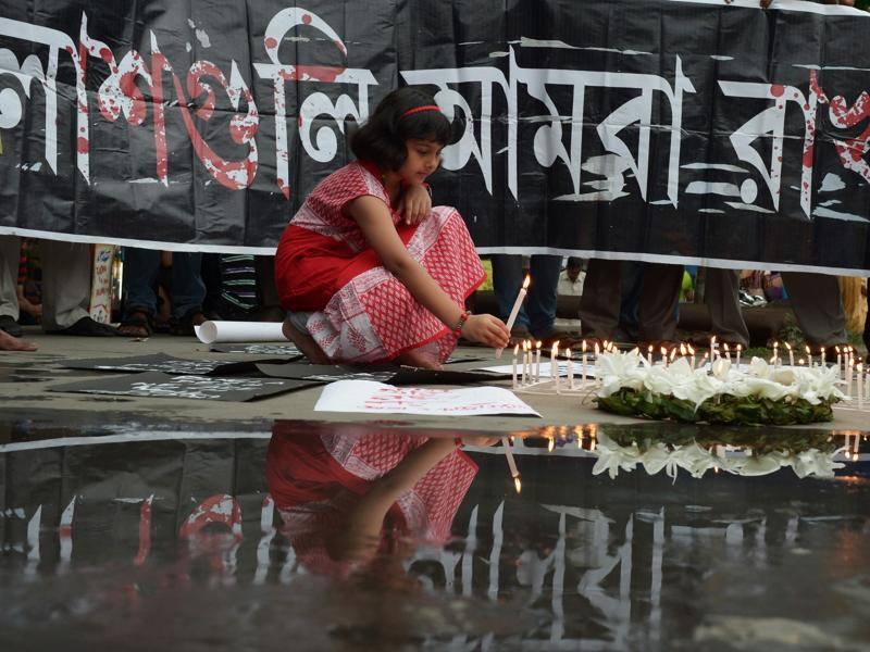 A girl lights candles at a protest against the Dhaka terror attack, in Kolkata on Saturday.  (AFP)