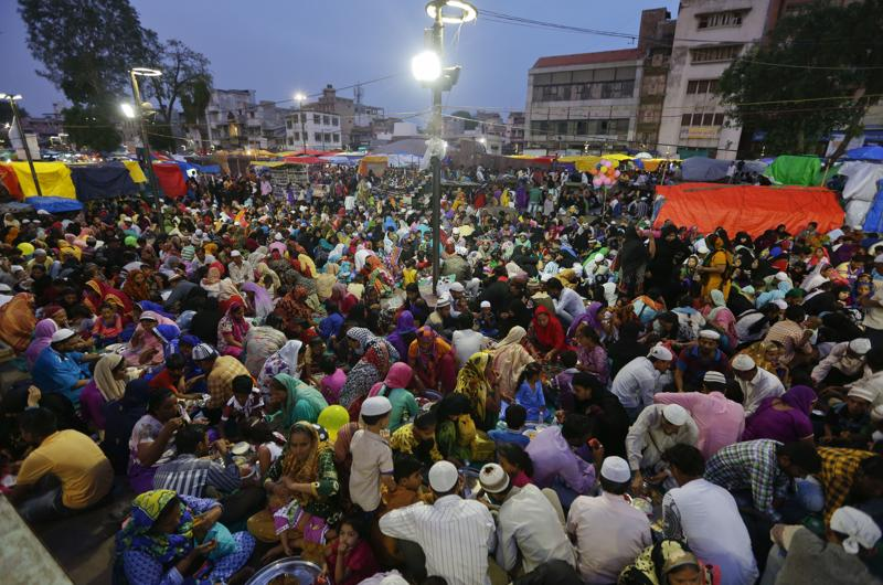 Muslims who arrived in the city for shopping on the last Sunday ahead of Eid al-Fitr, break their day long fast at a special Iftar hosted for them by traders at a market in Ahmadabad, India, Sunday, July 3, 2016.  (AP)