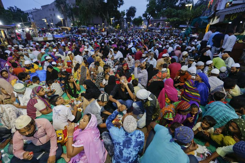 Muslims who arrived in the city for shopping on the last Sunday ahead of Eid al-Fitr, break their day long fast at a special Iftar hosted for them by traders at a market in Ahmadabad. (AP)