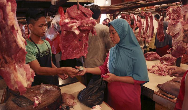A Muslim woman shops for meat during the last few days of the holy fasting month of Ramadan at a market in Jakarta, Indonesia, Monday, July 4, 2016. (AP)