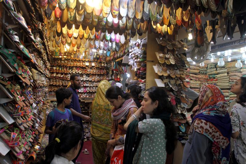 Pakistani women buy shoes for the upcoming Eid al-Fitr holiday to mark the end of the holy fasting month of Ramadan in Karachi, Pakistan, Sunday, July 3, 2016.  (AP)