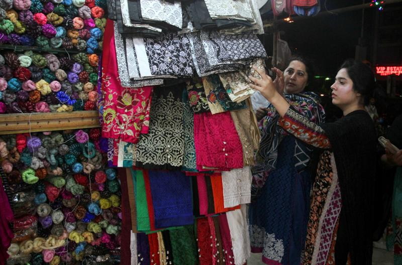 Pakistani women buy matching shawl with their new clothes for the upcoming Eid al-Fitr holiday to mark the end of the holy fasting month of Ramadan in Karachi, Pakistan, Sunday, July 3, 2016.  (AP)
