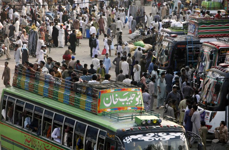 People travel on the rooftop of a passenger bus to reach their destinations for the upcoming Eid al-Fitr holiday, in Lahore, Pakistan, Sunday, July 3, 2016.  (AP)