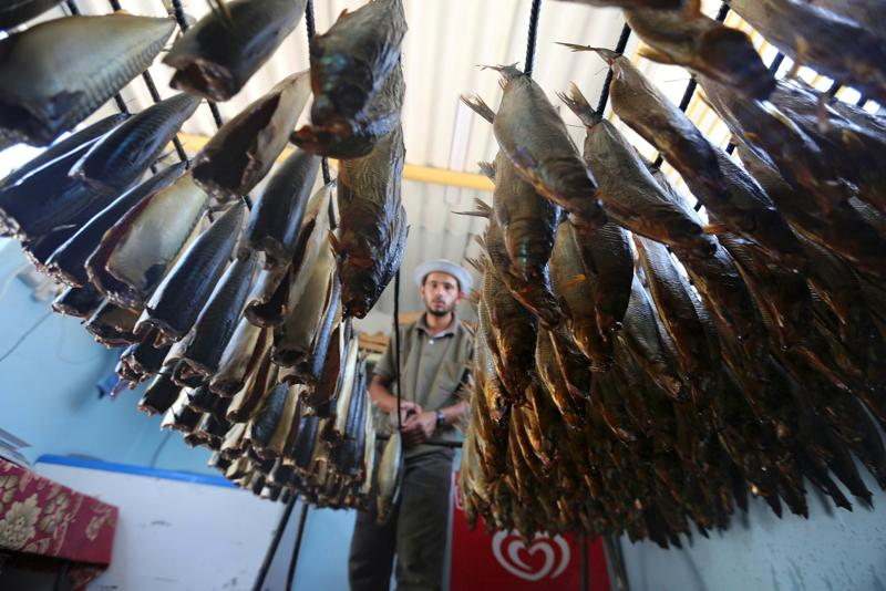 A Palestinian man prepares salted fish to be sold in a market ahead of the Eid al-Fitr holiday marking the end of Ramadan, in Khan Younis, in the southern Gaza Strip. (REUTERS)