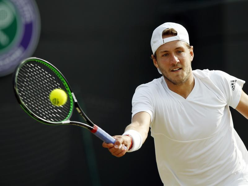 Lucas Pouille returns serve to Tomas Berdych. (AP)