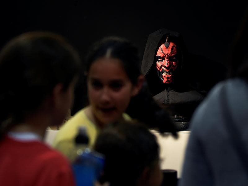 People visit a Star Wars exhibition at the Metropoli on July 1, 2016 as a cosplayer glowers behind.  (REUTERS)