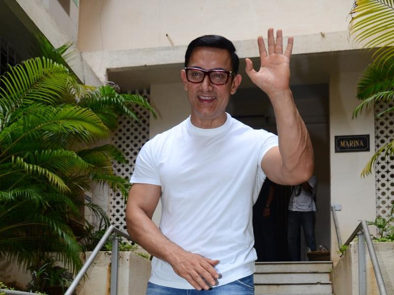 Aamir sports a casual look with a white T shirt and blue jeans.  (Viral Bhayani)
