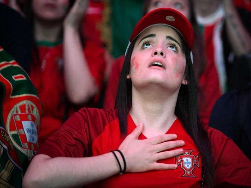 A Portugal supporter reacts as she watches, on a giant screen, the Euro 2016 semifinal football match between Portugal and Wales at the fan zone of the Champ de Mars in Paris. (AFP Photo)