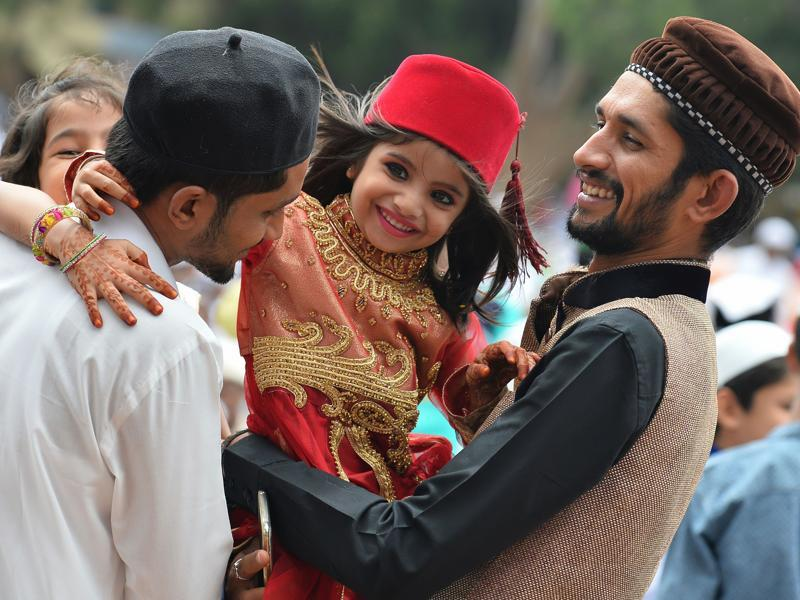 A young Indian Muslim girl hugs her elders after Eid-al-Fitr prayers at Chamrajpet Idgah Maidan in Bangalore on Thursday. The three-day festival, which begins after the sighting of a new crescent moon, marks the end of the fasting month of Ramadan during which devout Muslims abstain from food and drink from dawn to dusk.  (Manjunath Kiran/AFP)