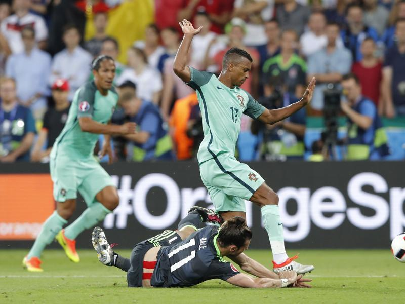 Gareth Bale crashes to the ground in a challenge with Portugal's Nani. (AP Photo)