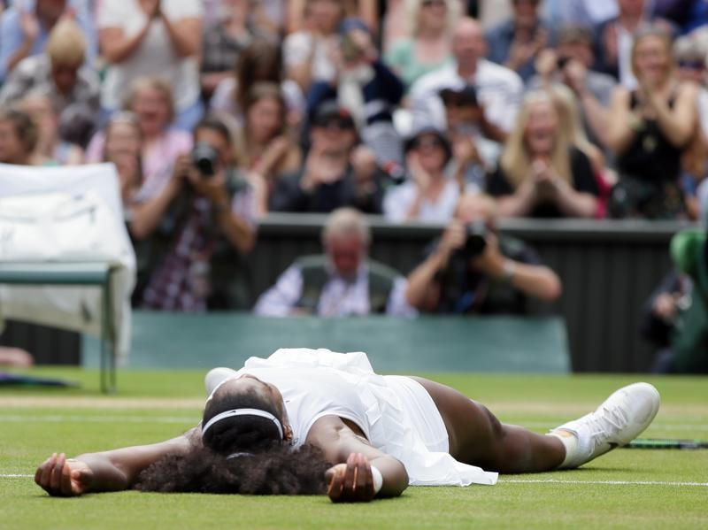 Serena lies flat on the grass in celebration of her win. (AP)