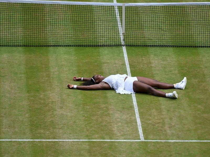 Serena falls to the grass in celebration of her win. (REUTERS)