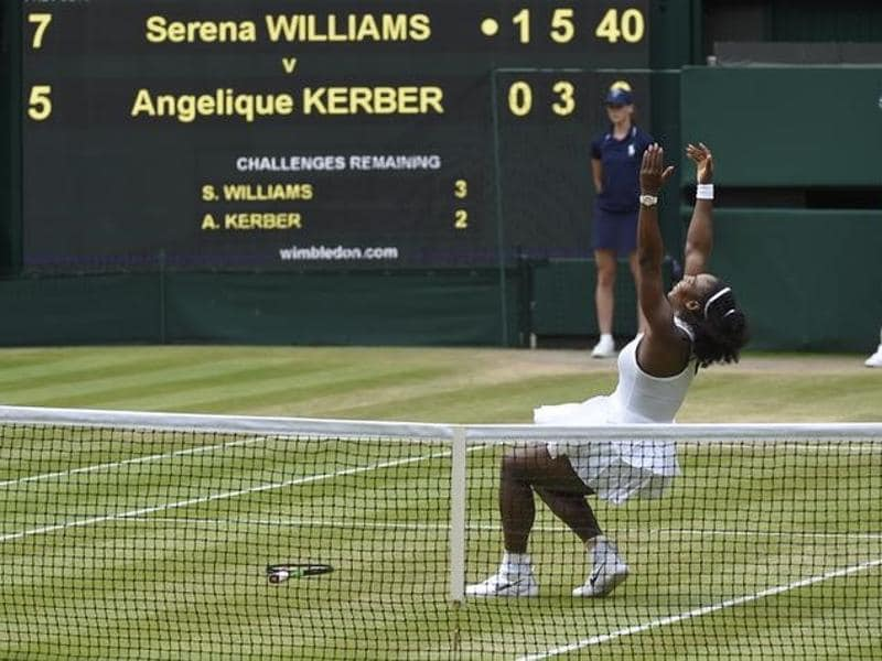 Serena lets go of her racquet and falls on the grass of Centre Court after her win. (Reuters)