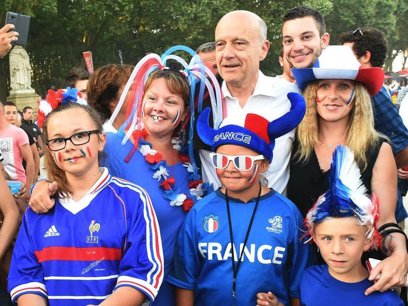 Former French Prime Minister, presidential candidate and Mayor of Bordeaux Alain Juppe poses with a French fan family. (AFP Photo)