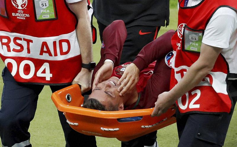 Portugal's Cristiano Ronaldo covers his face as he is stretchered off the pitch after suffering an injury. (AP Photo)