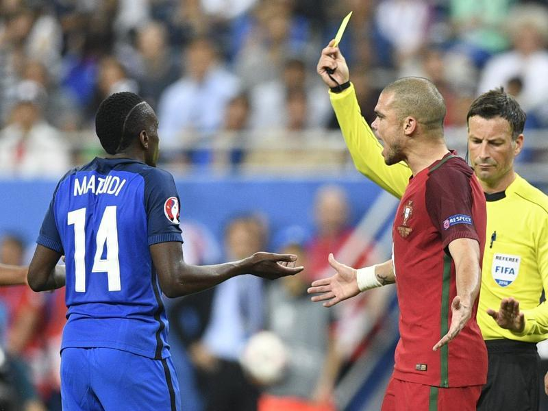 English referee Mark Clattenburg shows a yellow card as France's midfielder Blaise Matuidi and Portugal's defender Pepe react during the Euro 2016 final. (AFP Photo)