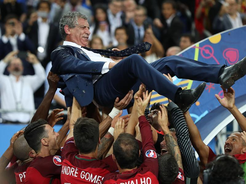 Portugal's coach Fernando Santos is held up by his players as they celebrate after beating France during the Euro 2016 final football match at the Stade de France in Saint-Denis. (AFP Photo)