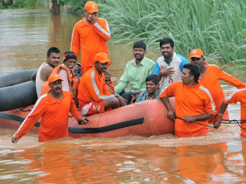 NDRF personnel evacuating stranded people from a flooded village in Kolhapur. (HT PHOTO)