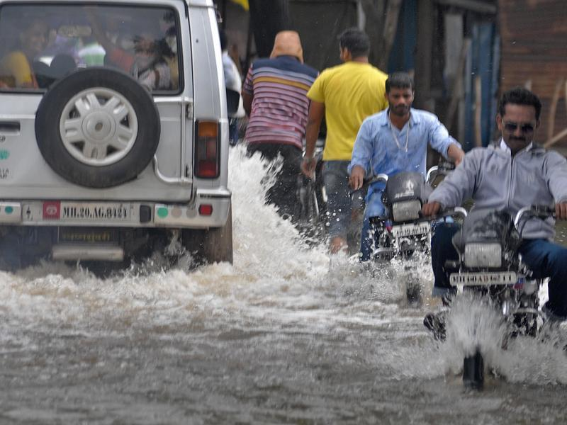 Local residents struggle through  submerged roads in Sangli  on Wednesday. (UDAY DEOLEKAR)