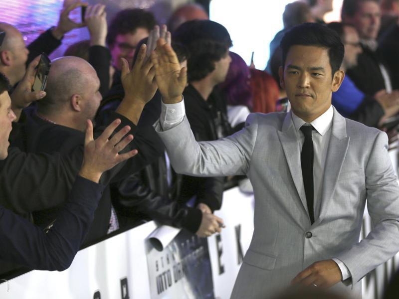 Actor John Cho, who plays Hikaru Sulu, hi-fives fans as he walks on the red carpet during the premiere of the film Star Trek Beyond. (AP)