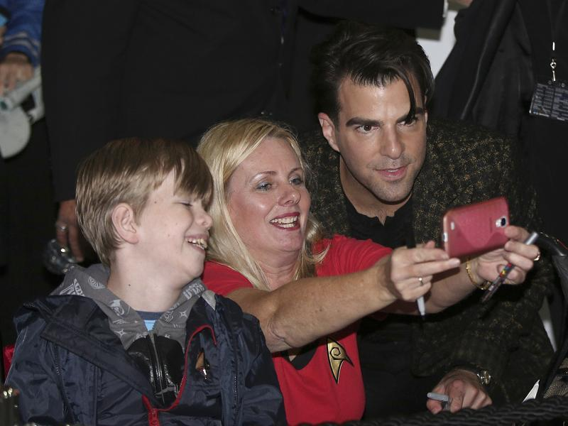 Zachary Quinto, who plays Spock, has a selfie taken with a fan as he walks on the red carpet during the premiere of the film Star Trek Beyond. (AP)