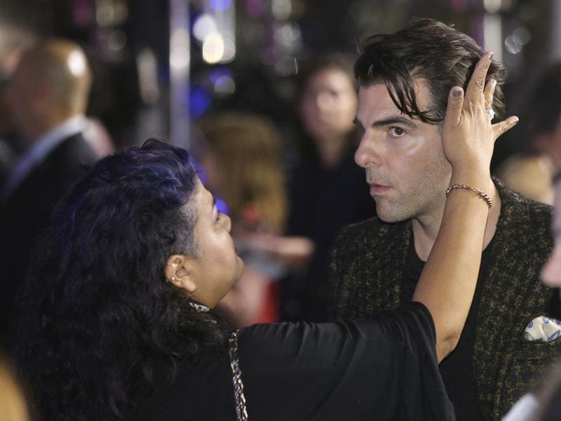 Actor Zachary Quinto, right, has his hair adjusted as he walks on the red carpet during the premiere of the film