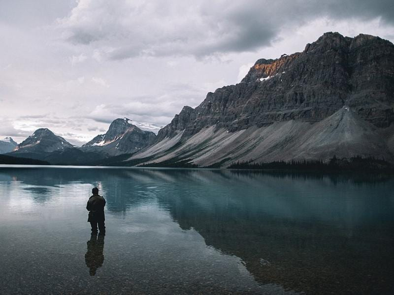 Though he usually uses a timer to shoot himself he was lucky to see a fisherman he could use for a model instead while photographing Bow Lake in Canada. (Instagram)
