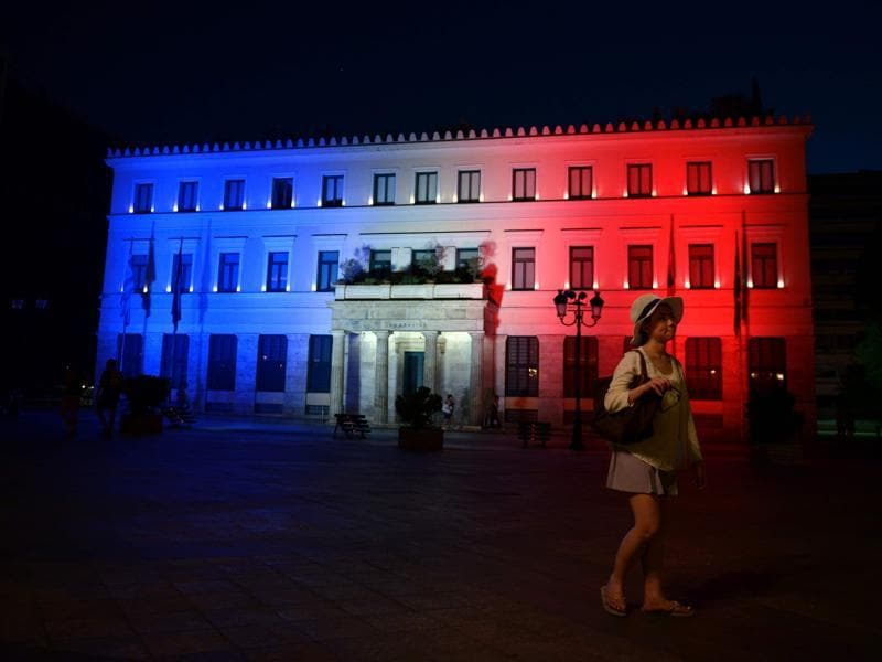A woman walks past Athens' City Hall, illuminated with the colours of the French flag in tribute for the victims of the attack in Nice, in Athens.  (AFP Photo)