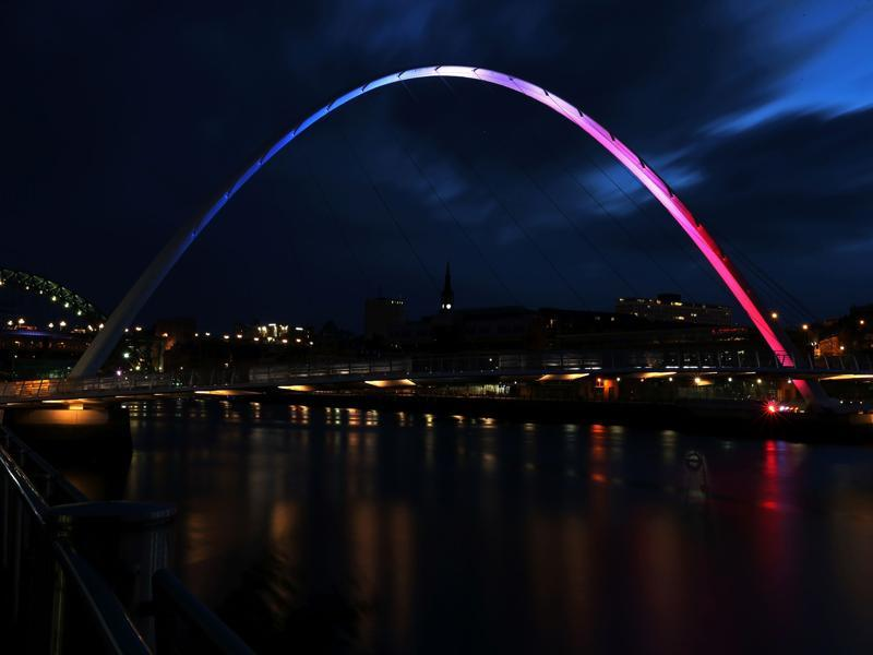 The Gateshead Millennium Bridge is illuminated in blue, white and red lights, in Newcastle, northeast England. (AFP Photo)