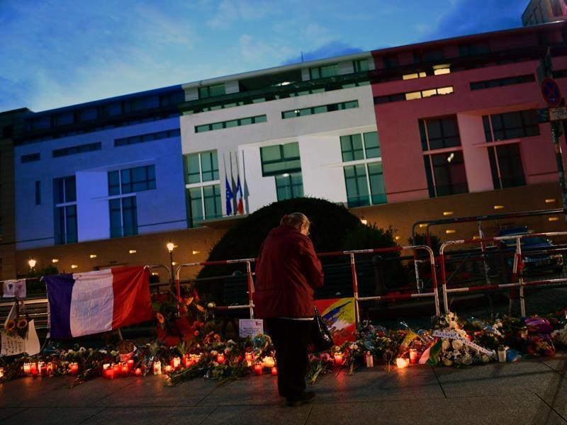 The French embassy is illuminated in the colours of the French tricolor in Berlin as wellwishers left flowers and candles. (AFP Photo)