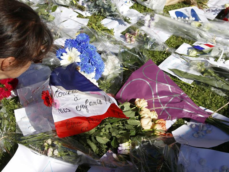A woman is seen near flowers and a flag placed in tribute to victims two days after an attack by the driver of a heavy truck who ran into a crowd on Bastille Day. (Reuters Photo)