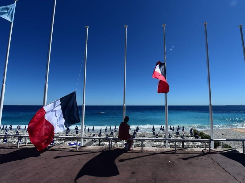 A woman sits under French flags lowered at half-mast in Nice, following the deadly Bastille Day attack. (AFP Photo)