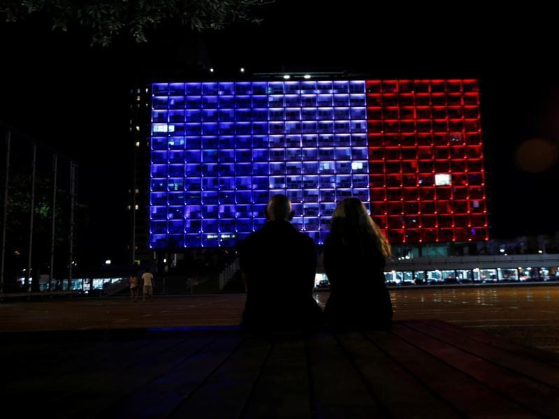 An Israeli couple watches the Tel Aviv city hall as it is lit up in the colours of the French flag in tribute to the attack victims of Nice, in Tel Aviv, Israel. (Reuters Photo)