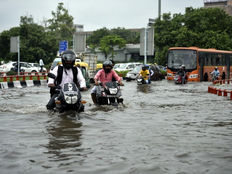 Commuters struggle through waterlogged roads after heavy rains, near AIIMS. (Arun Sharma/HT PHOTO)