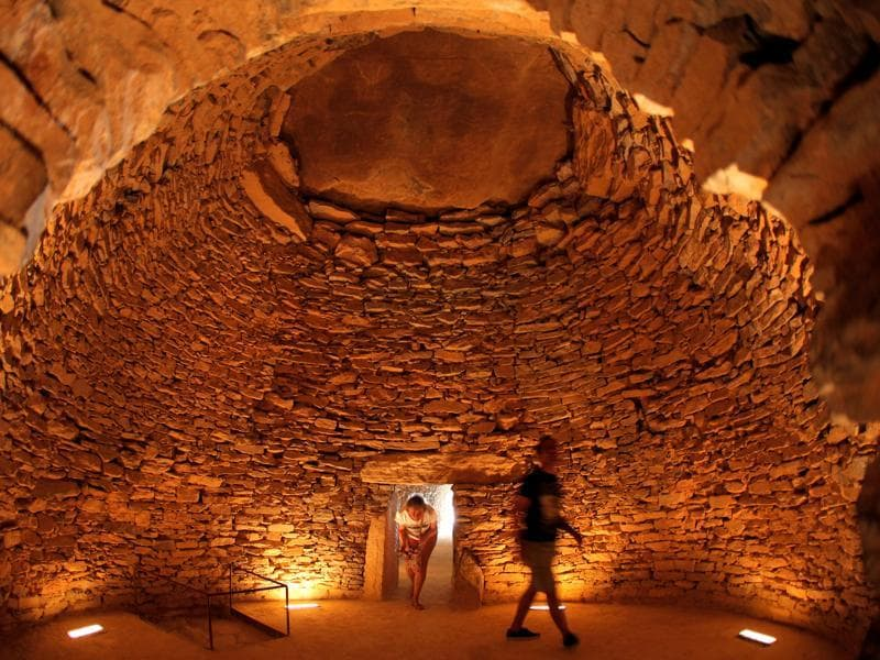 People walk inside the Tholos de El Romeral dolmen at Antequera Dolmens Site, which was recently named a UNESCO World Heritage site during the 40th Session of the World Heritage Committee held in Istanbul in Antequera, southern Spain, July 17, 2016. (REUTERS)