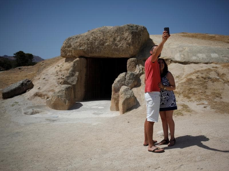 A dolmen is a megalithic (prehistoric) tomb with a large flat stone laid on upright ones. A couple takes a selfie outside the Menga dolmen. (REUTERS)