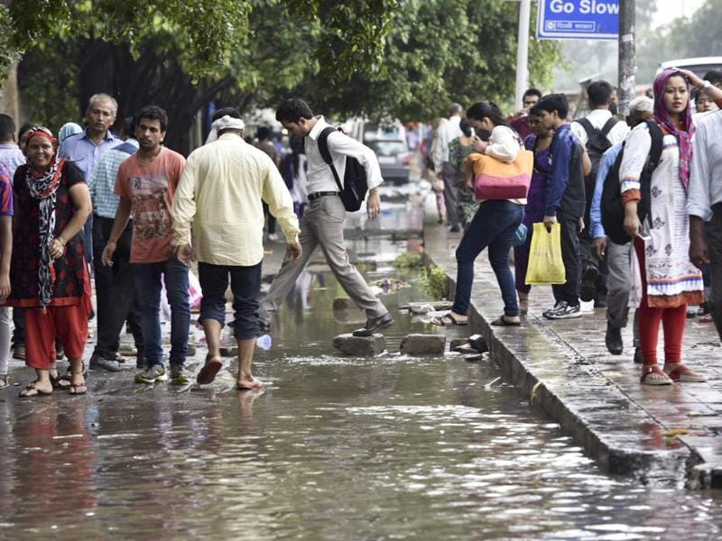 People wade through a water logged street near AIIMS.  (Saumya Khandelwal/HT Photo)