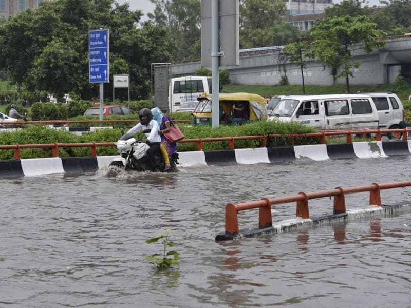 Commuters navigate through a water logged road near AIIMS. (Saumya Khandelwal/HT Photo)