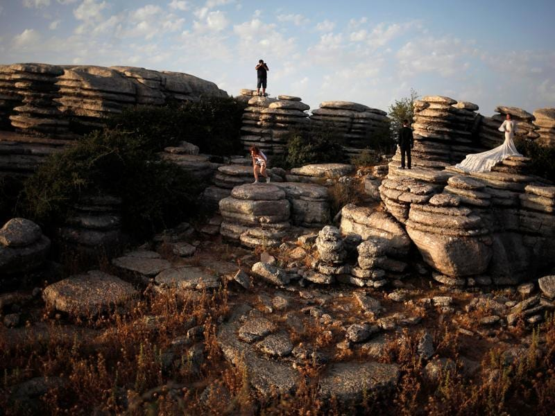 A newly married couple poses for a wedding photographer on the mountainous formations of El Torcal nature park at site. These sites are megalithic monuments made up of the Menga and Viera dolmens and the tholos (a dome-shaped tomb of ancient Greek origin, especially one dating from the Mycenaean period) of El Romeral. (REUTERS)
