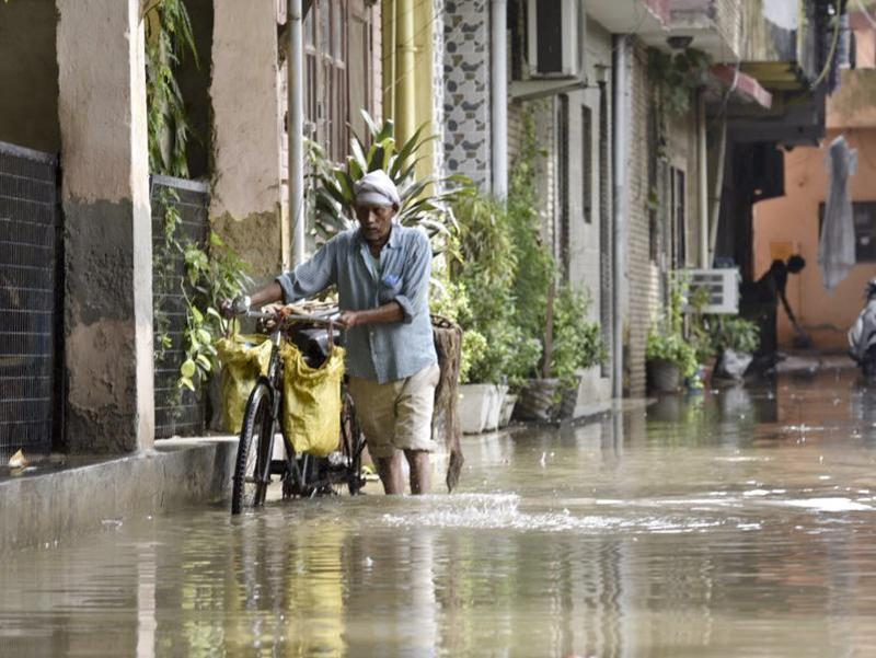 A man wades through a water logged street in Nehru Nagar.  (Saumya Khandelwal/HT Photo)
