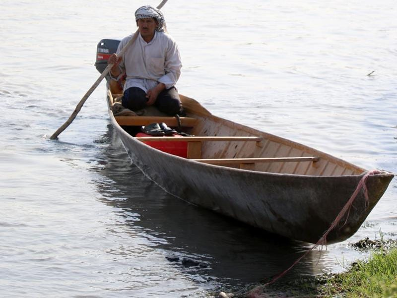 An Iraqi man rides a boat. The marshlands are one of the world's largest inland delta systems. (AFP)