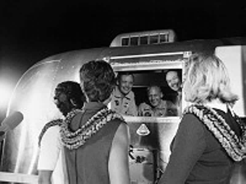 Apollo 11 astronauts, still in their quarantine van, are greeted by their wives upon arrival at Ellington Air Force Base.  (NASA)