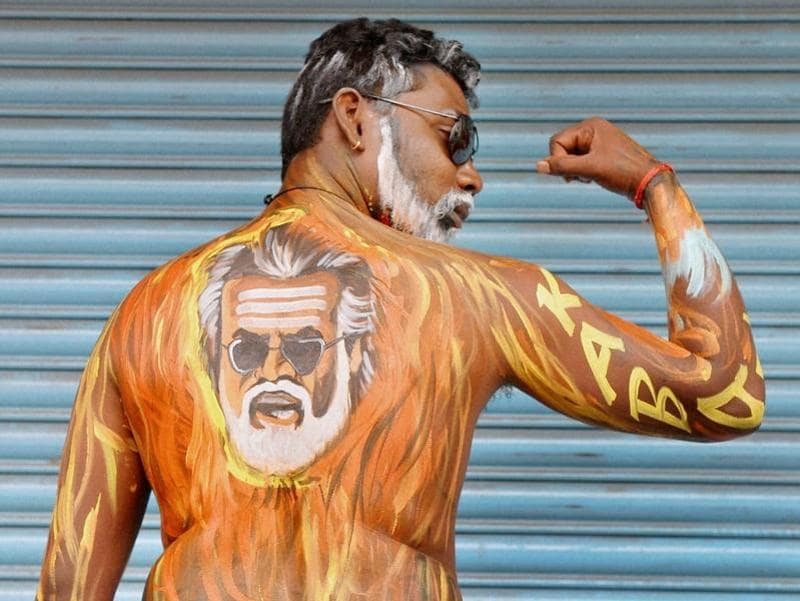 A fan in Bengaluru sports Rajinikanth's face painted on his body as the actor's film Kabali hit the theatres today.  (PTI)