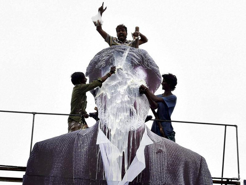 Fans pouring milk on a giant poster of actor Rajinikanth in celebration of the release of  his film, Kabali, in Chennai on Friday.  (PTI)