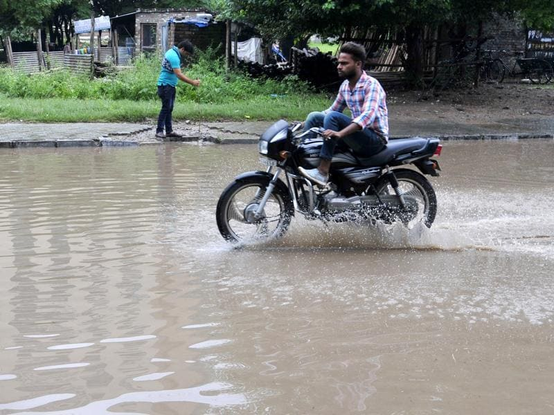 A Mohali resident crossing a street on his bike after heavy morning shower on Saturday. (Ravi Kumar/HT Photo)