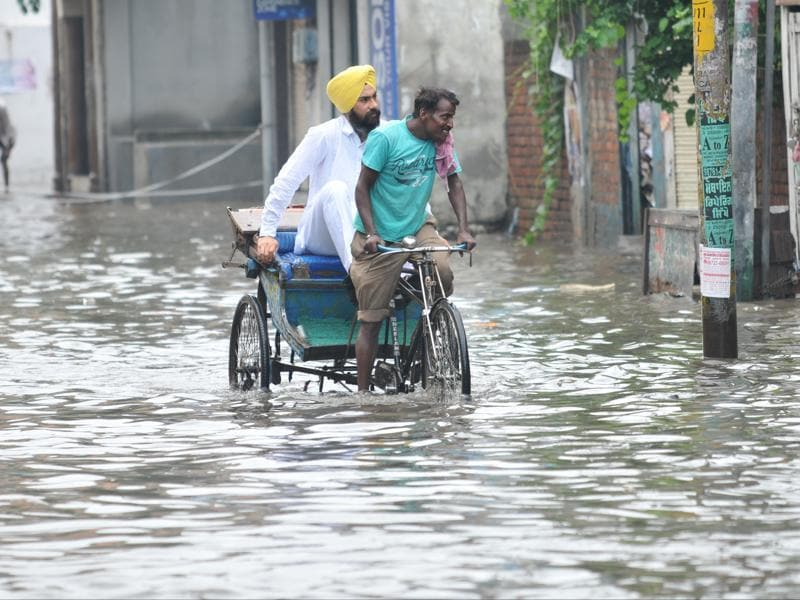 A rickshaw puller paddling through the waterlogged road in Jalandhar on Saturday. (Pardeep Pandit/HT Photo)